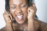 African American woman singing and wearing headphones
