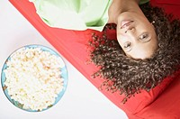 African American woman laying on sofa with popcorn
