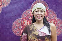Asian woman smiling in front of tapestry