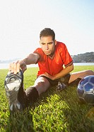 Soccer player stretching in field