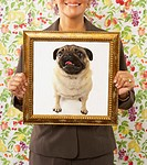 Woman holding framed picture of dog