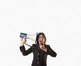 Businesswoman shouting into megaphone pointed at her head