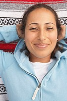 Portrait of woman laying on blanket smiling