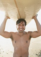 Portrait of man balancing surf board on head