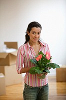Young adult woman holding potted flowers