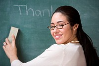 Portrait of female teacher erasing chalkboard