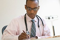 Male doctor writing notes