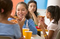 Four girls eating pizza in cafeteria