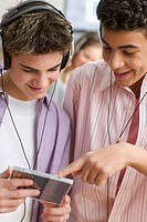 Two teenage boys with headsets listening to music