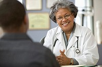 Mature female doctor sitting at desk with male patient