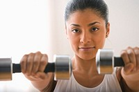 Portrait of woman holding dumbbells in front of her