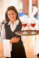 Waitress carrying tray with wine glasses