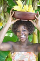 Portrait of woman smiling with bowl of bananas balanced on head