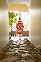 Woman in kimono walking on spa pathway