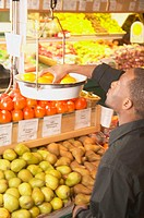 African American man weighing fruit in supermarket scale