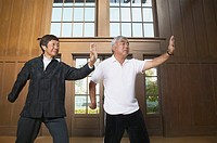 Senior Asian couple practicing Tai Chi indoors, Berkeley, California, United States