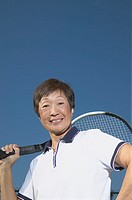 Senior Asian woman with tennis racket