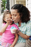 Daughter feeding her mother ice cream
