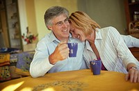 Happy Couple Enjoying Cup of Coffee at Kitchen Table