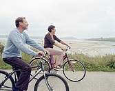 Senior couple riding bicycles by sea, smiling, side view (focus on woman)