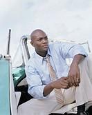 Businessman sitting in convertible with door open, looking away