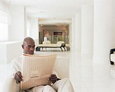 Businessman relaxing in hotel lobby, reading newspaper, portrait