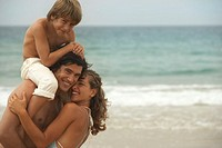 Family on beach with son (8-10) on father´s shoulders, smiling, portrait