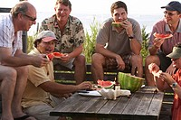 Group of men sitting around table on beach front eating watermelon