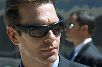Close Up of a Businessman Wearing Sunglasses and a Businessman in the Background