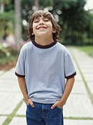 Boy (5-7) standing in garden with hands in pockets, smiling