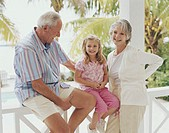 Grandparents on balcony with granddaughter (3-5) smiling