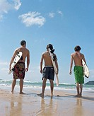 Three men standing on wet sand holding surfboards, rear view