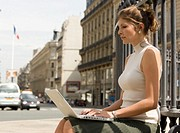 Woman sittiing on bench in street using laptop