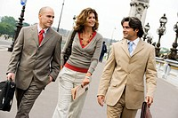 Businesswoman and two businessmen walking together on street, smiling
