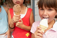 Three girls (6-9) with ice creams, one licking ice cream, portrait