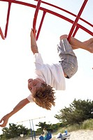 Boy (6-8) hanging upside down on climbing frame, portrait