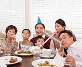 Three generational family with party blowers at dinner table, portrait