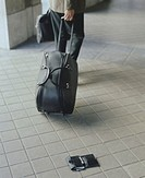 Mature businessman with suitcase, wallet on floor (Digital Composite)