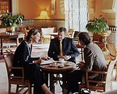 Two businessmen and businesswoman gathered around small table