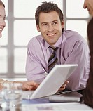 Businessman in meeting with colleagues, smiling