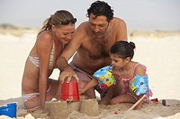 Couple on beach building sandcastles with daughter (2-4)