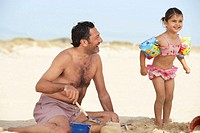 Girl (2-4) on beach wearing arm bands, standing next to father