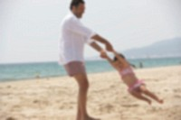Man swinging daughter (2-4) on beach (defocussed)