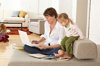 Woman using laptop on sofa by daughter (2-4) smiling