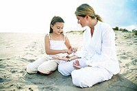 Mother and daughter (6-8) on beach, girl lining shells on mother´s arm
