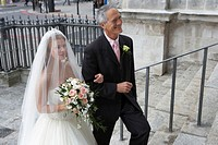 Father escorting bride up steps to church, smiling, elevated view