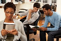 Female office worker reading, two male colleagues looking at book