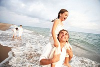 Family on beach, daughter (6-8) sitting on father´s shoulders, smiling