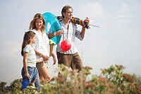 Parents and daughter (6-8) on path carrying beach toys and parasol