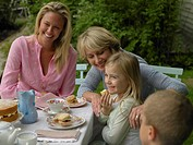 Girl (6-8) at garden table with mother and grandmother, smiling